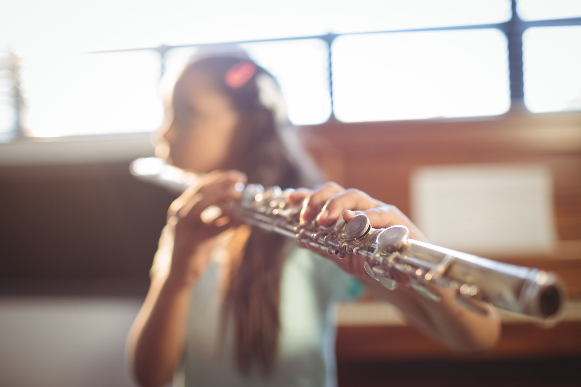 Girl practicing flute in classroom