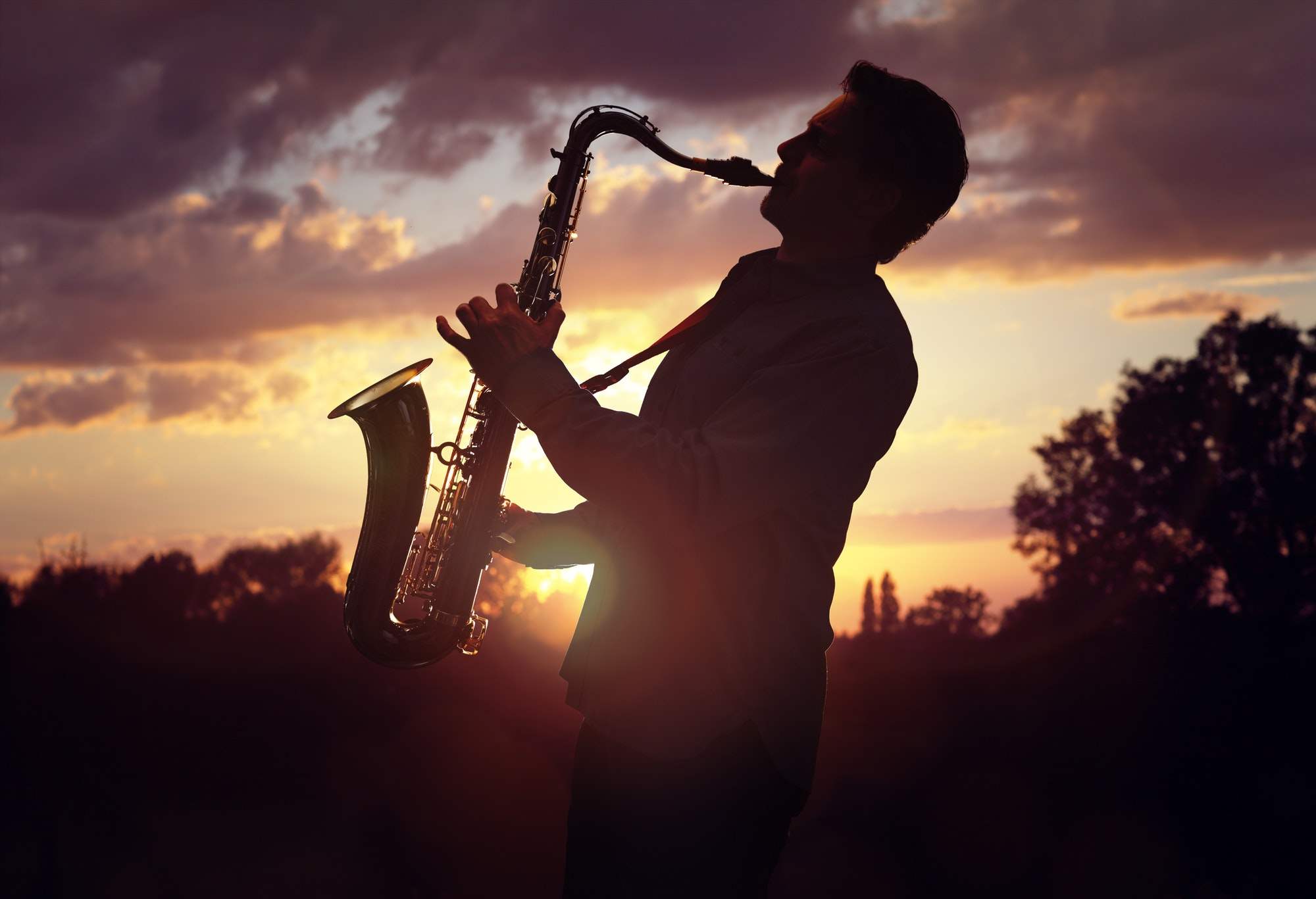 Saxophonist playing sax against sunset