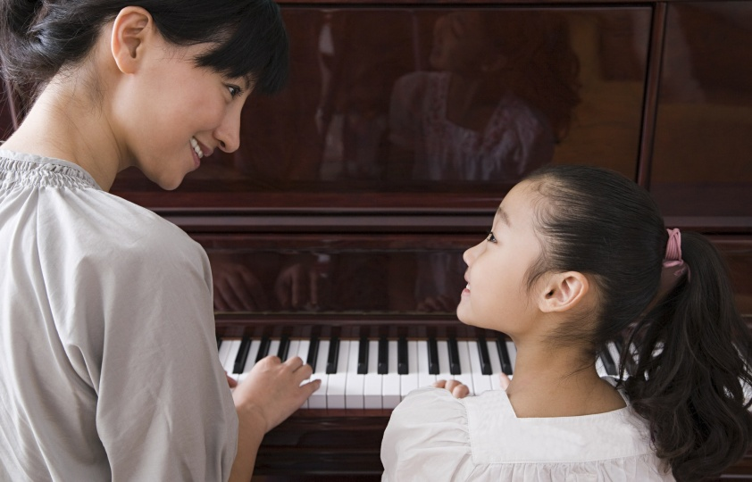 Mother and daughter playing the piano