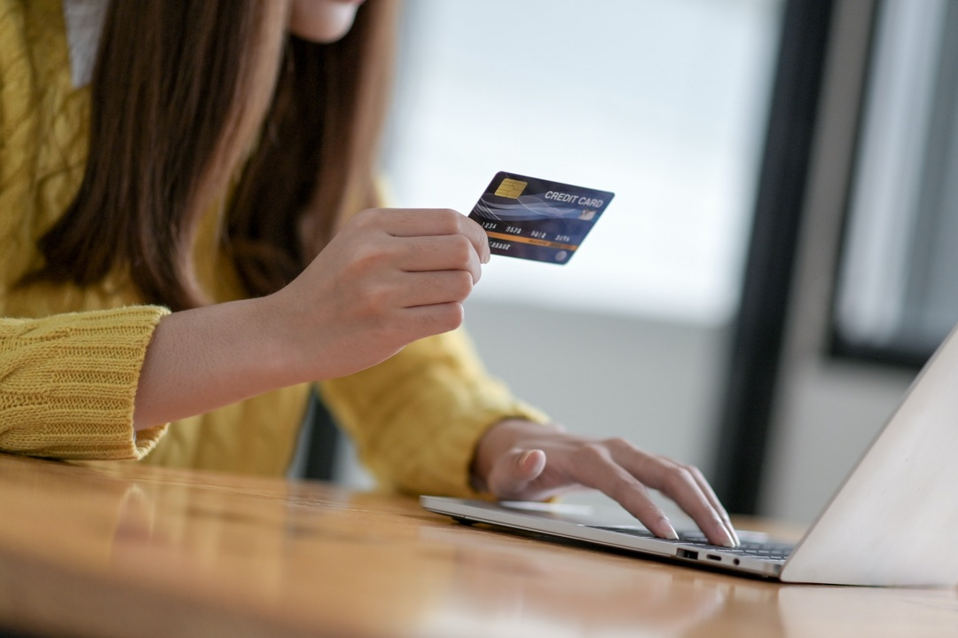 Young women are using a laptop for online shopping and credit card payments.